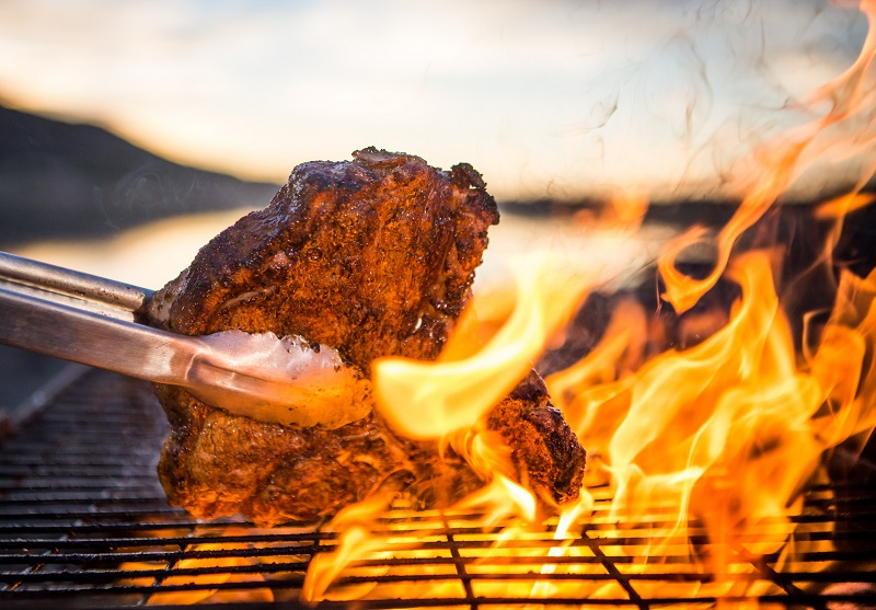 A t-bone steak being char-grilled over open flames on a commercial gas grill