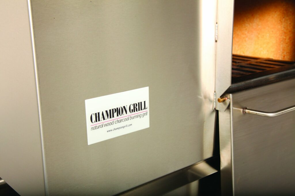 CHAMPION GRILL natural wood/charcoal burning grill label on grill